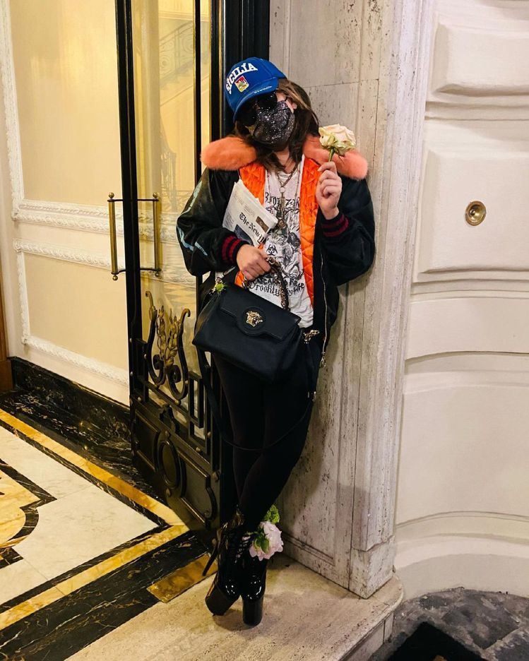 Lady Gaga身穿GUCCI T羊毛翻領飛行員外套、挽著VERSACE手袋,...