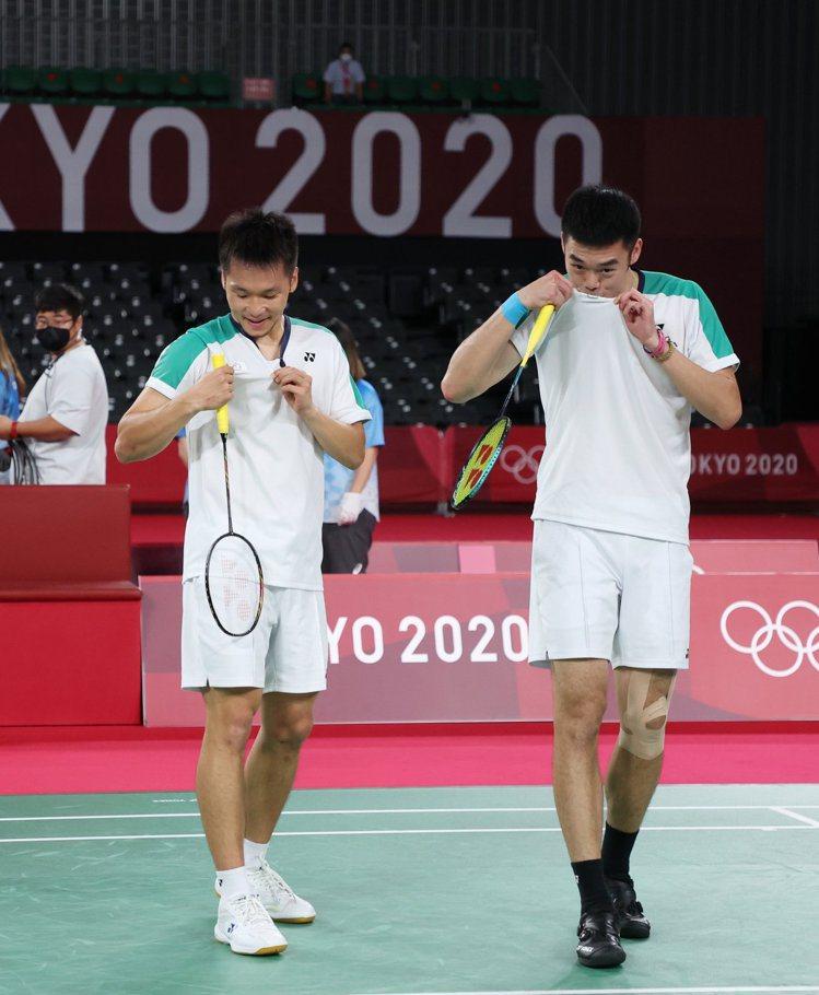 在奪下金牌後李洋(左)和王齊麟秀出隊服上的奧會徽章。特派記者余承翰/東京攝影