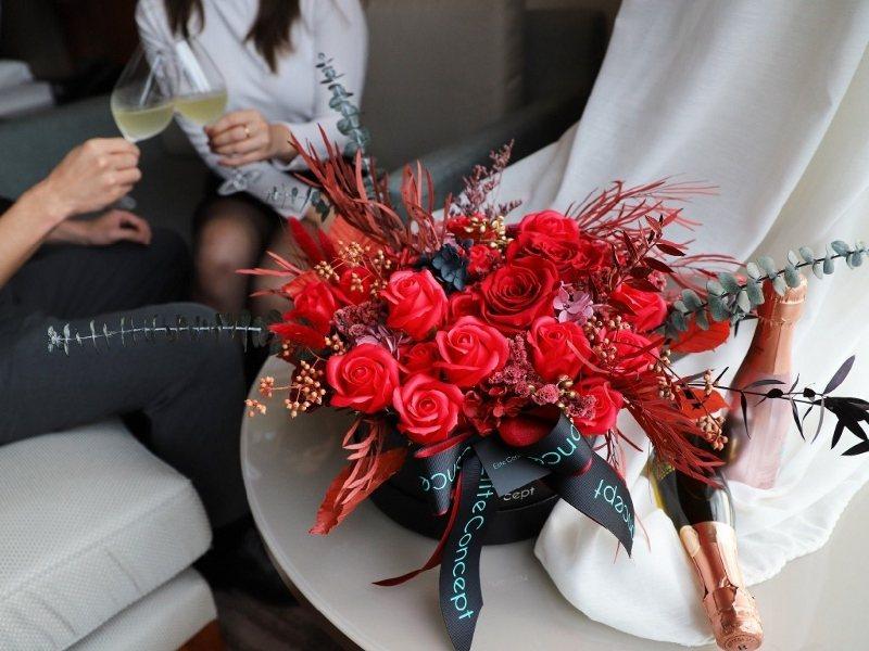 朵朵盛開的玫瑰香皂花,圍繞著象徵永恆的永生玫瑰,鮮豔的紅玫瑰色與成穩的黑色禮盒相...