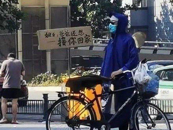 鄭州地鐵淹水事故後,一名父親穿著雨衣牽著腳踏車,在沙口路站外頭守候的身影在網上流傳。圖/取自微博