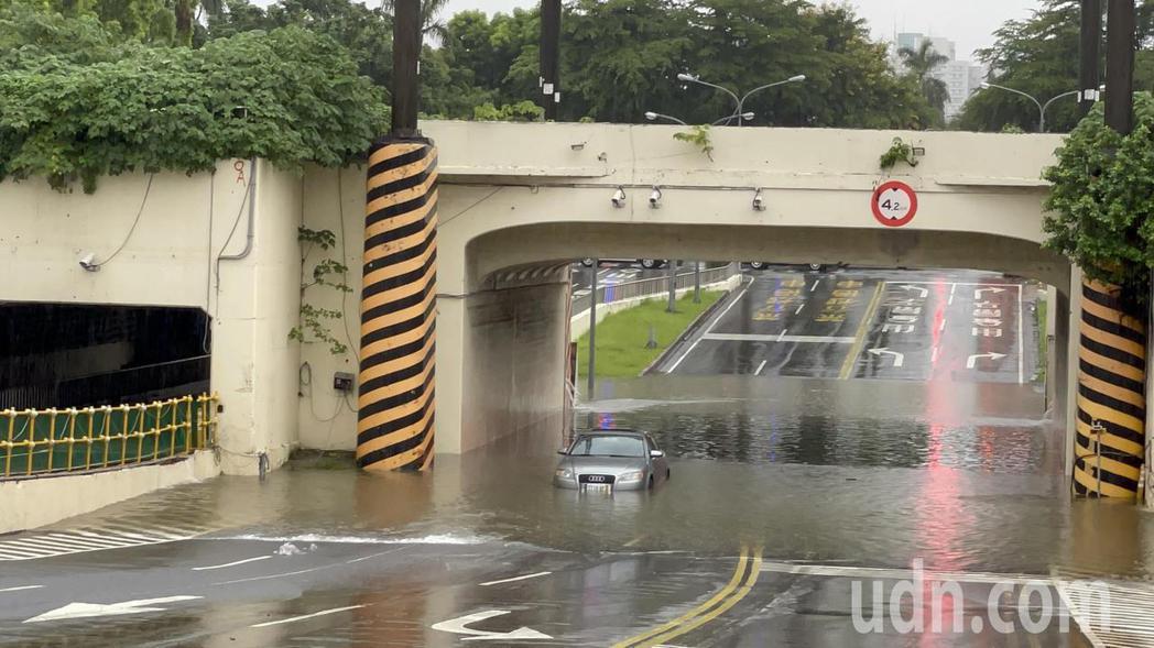 台南市上午降下豪雨,小東路地下道積水,有轎車行經積水處熄火,見狀及時逃出轎車才未...