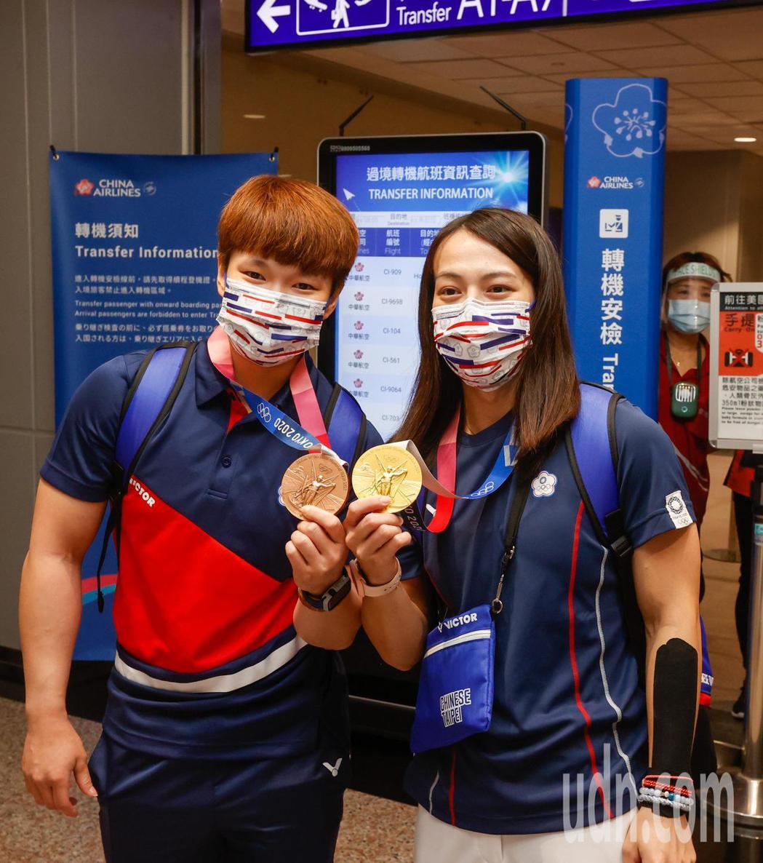 奪得奧運舉重金牌的郭婞淳(右)及銅牌的陳玟卉(左)傍晚返抵國門,兩人開心地秀出獎...