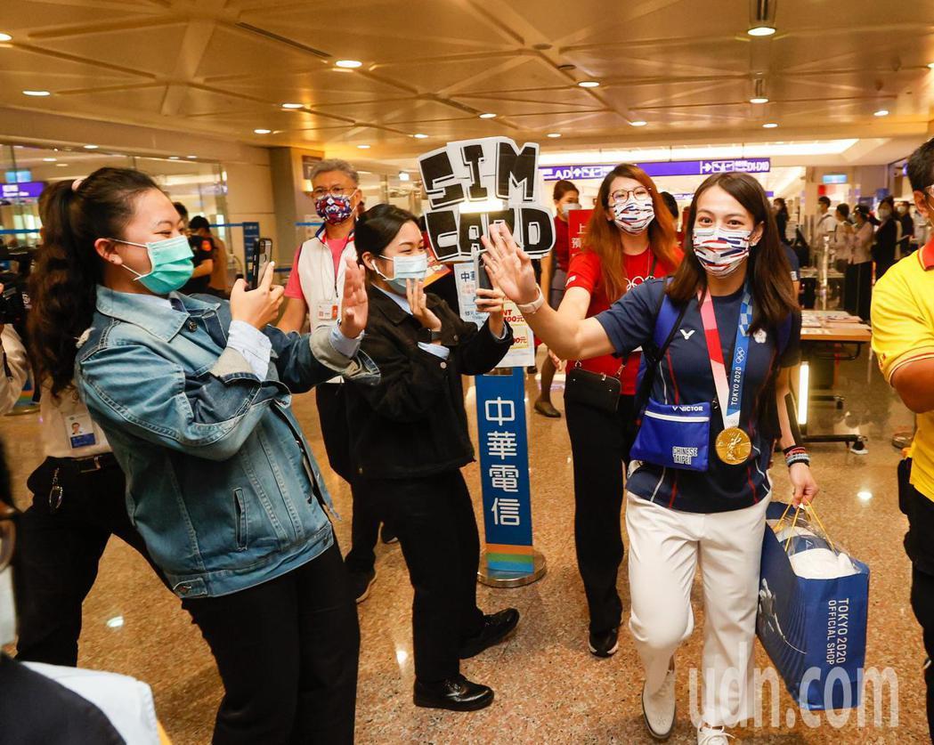 奪得奧運舉重金牌的郭婞淳(右)傍晚回國,一路上有很多粉絲搶拍照並為她加油。記者鄭...