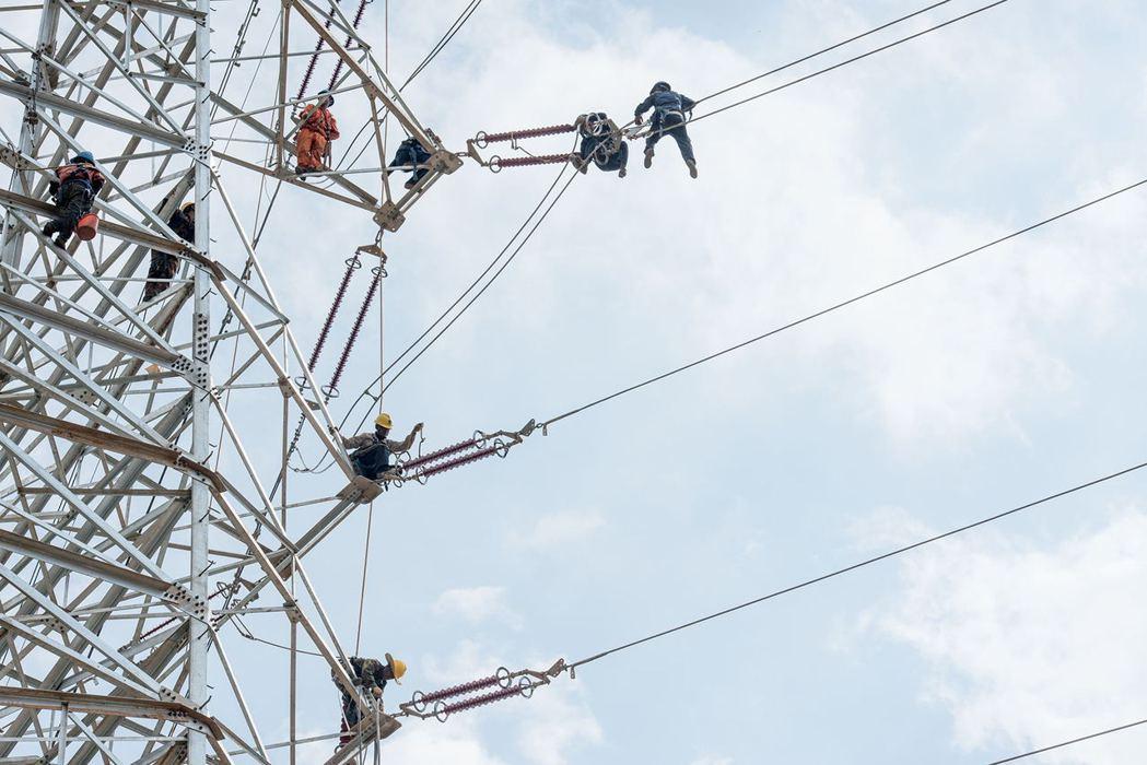 大陸發改委為完善分時電價機制,將推出尖峰電價和低谷電價機制,圖為電力工人維修設施...