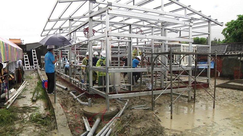 台灣希望義工團為幫鄭小妹圓夢,昨天頂著風雨趕工,在豬舍旁建造新屋,令人感動。記者蔡維斌/攝影