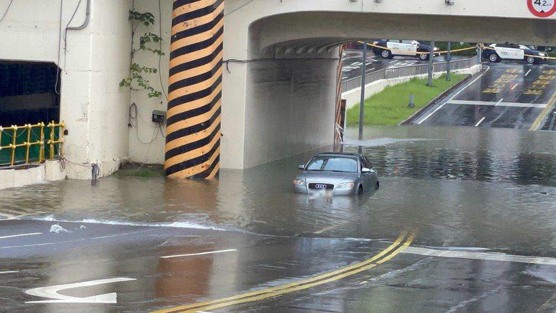 台南市區小東路地下道積水半個輪胎高,警方準備在地下道兩側拉起封鎖線,沒想到有車子闖入地下道而受困。記者邵心杰/攝影