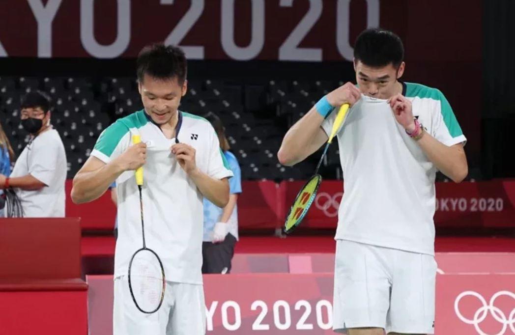我國羽球男子雙打選手李洋(左)和王齊麟,昨晚打贏冠軍戰後,開心拉起球衣上的梅花會...