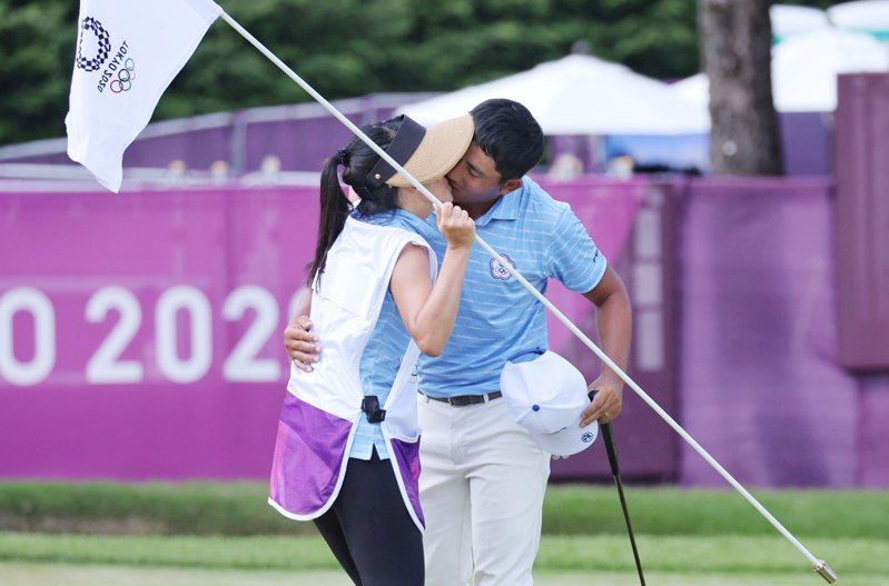 潘政琮(右)完成東奧四輪賽事後,在18洞果嶺親吻揹球袋的太太林盈君。特派記者余承翰/東京攝影
