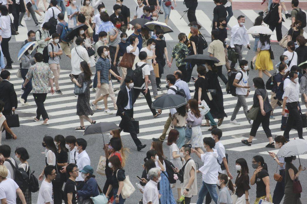 日本東京民眾7月28日戴口罩經過街頭。美聯社