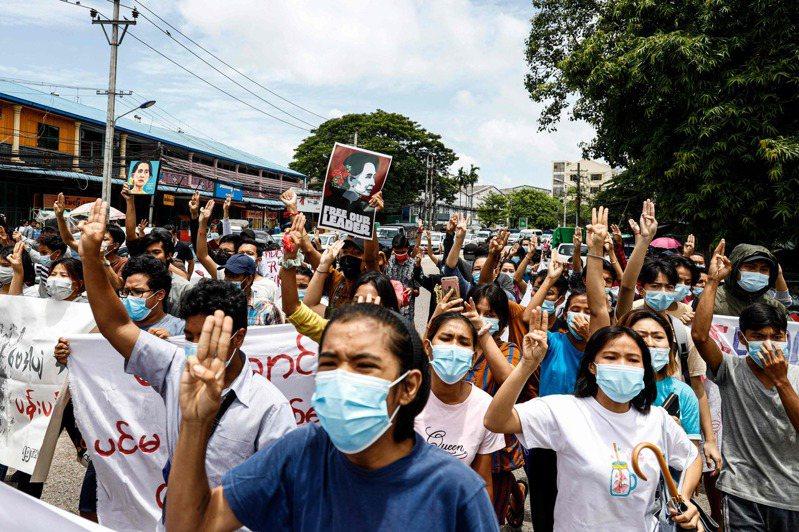 緬甸仰光示威者比出象徵支持民主的三指手勢。法新社