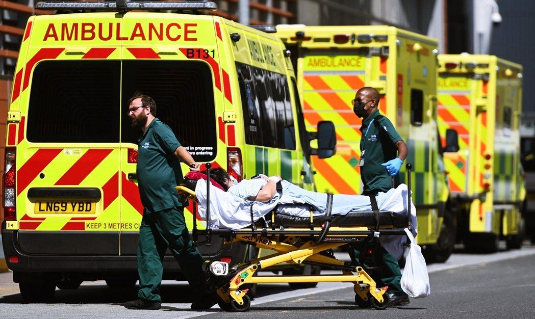 7月23日,英國倫敦皇家倫敦醫院外的救護車工作人員與一名患者。 圖/歐新社
