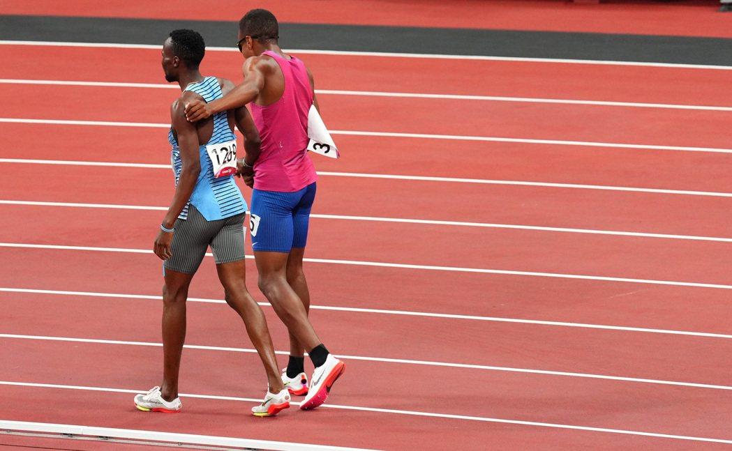朱特(右)與阿莫斯肩搭著肩,一起走完賽道。 路透