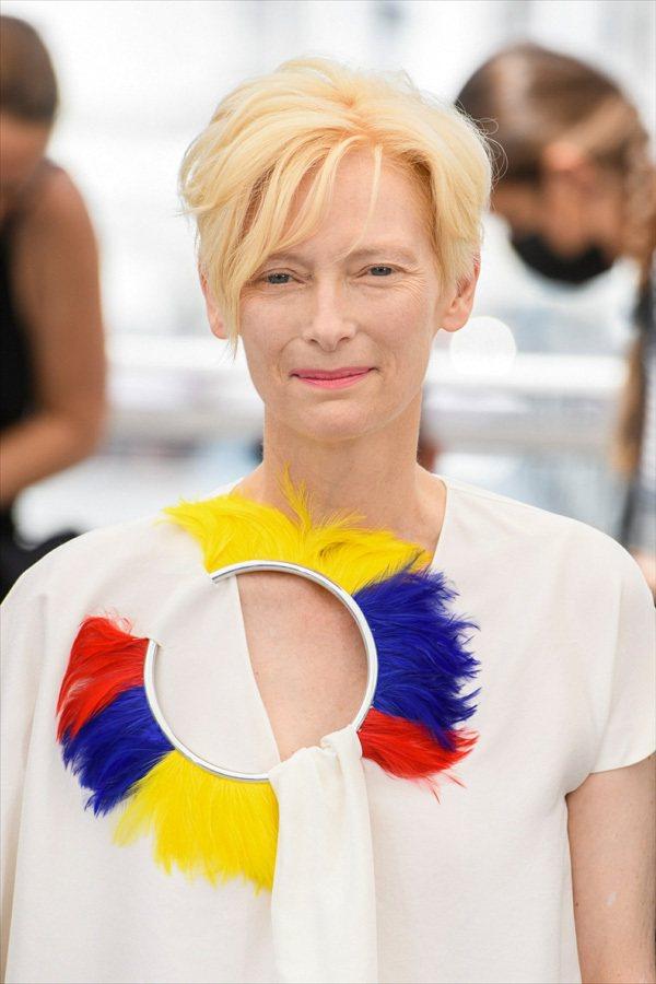 蒂妲史雲頓為了呼應白色衣服上的三色羽毛裝飾,選擇橘色系的唇膏,但眼妝也是幾乎沒有...