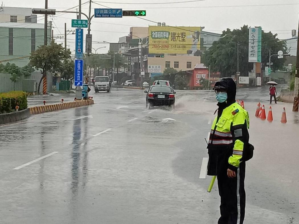 台中市今天持續大雨,沙鹿區沙田路和光華路段淹水,員警到場疏導交通。圖/警方提供