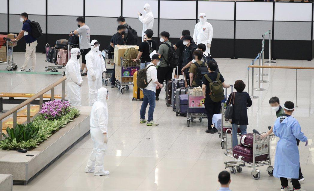 返國的南韓公民抵達仁川機場後,在檢疫人員引導下排隊。(歐新社)