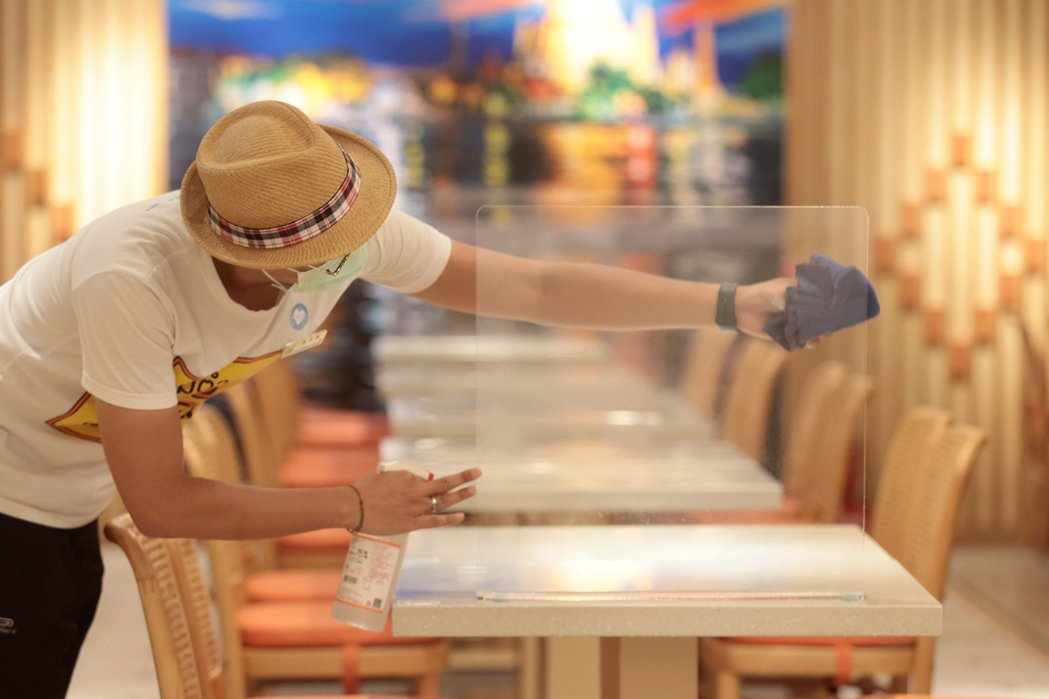 雙北市長柯文哲、侯友宜決定同步開放餐飲內用,許多餐飲業者將內用的隔板放置在餐桌上...