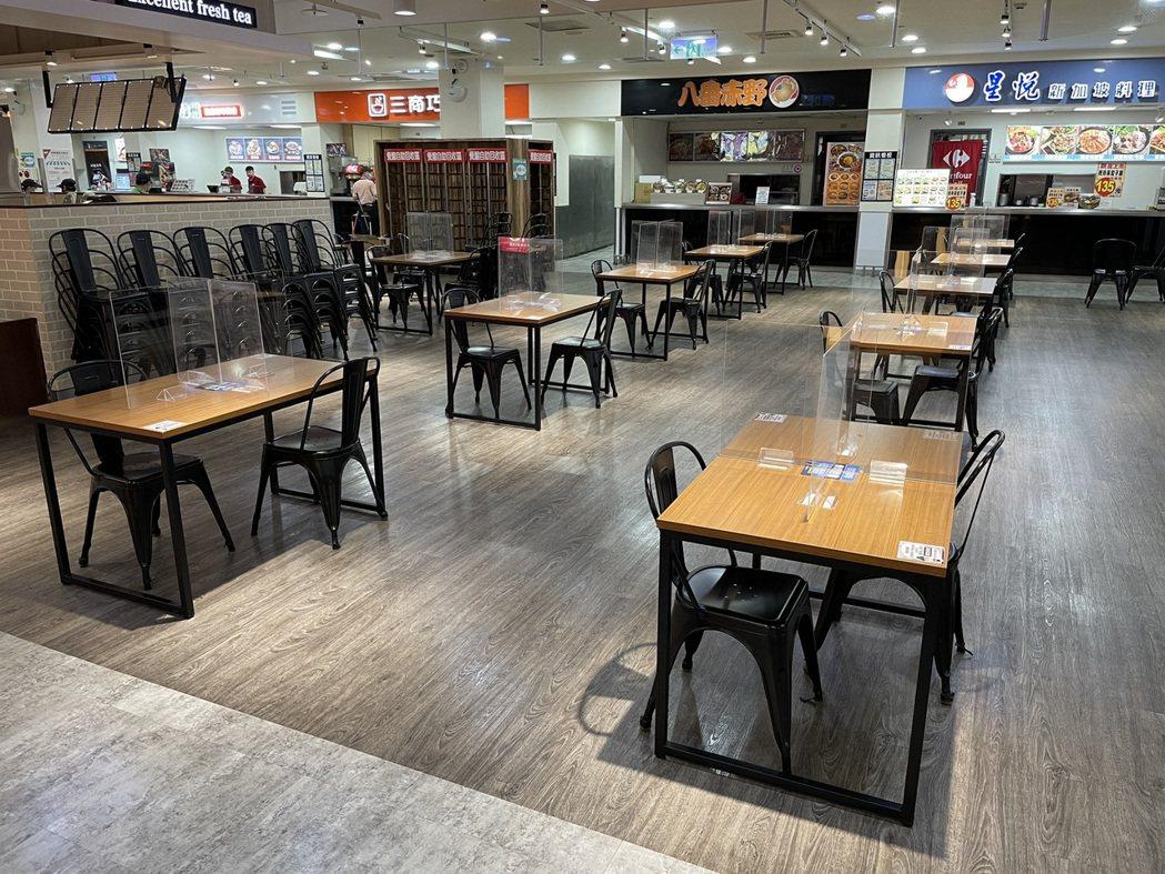 家樂福美食街混坐區進行容留管制,座位數減半,每桌並加設隔板、座位採梅花座。圖/家...