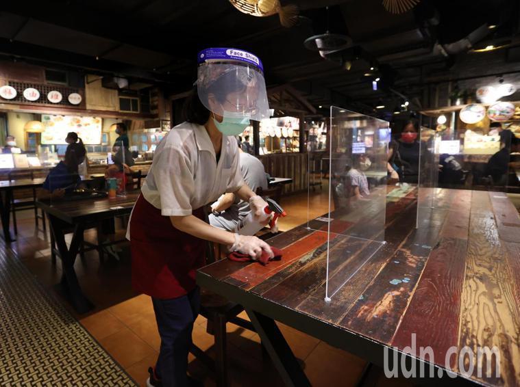 雙北餐廳今天起有條件開放內用,清潔人員在民眾用餐過後清潔消毒。記者林澔一/攝影