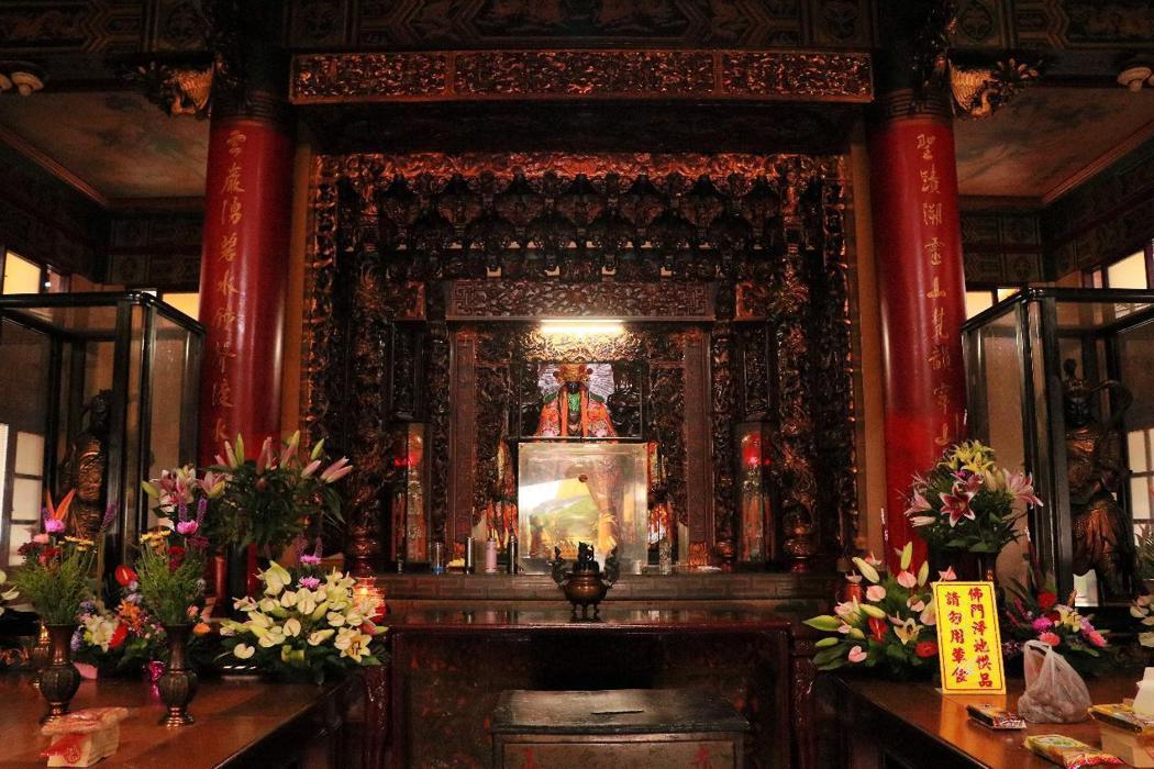 赤山龍湖巖正殿內部,佛龕前的玻璃罩中供奉彌勒佛,後方則為觀音「大媽」。不過在龍湖巖中資歷最老、輩分最高的是「老三媽」,而當初的靈石何在目前已難考證。 圖/作者自攝