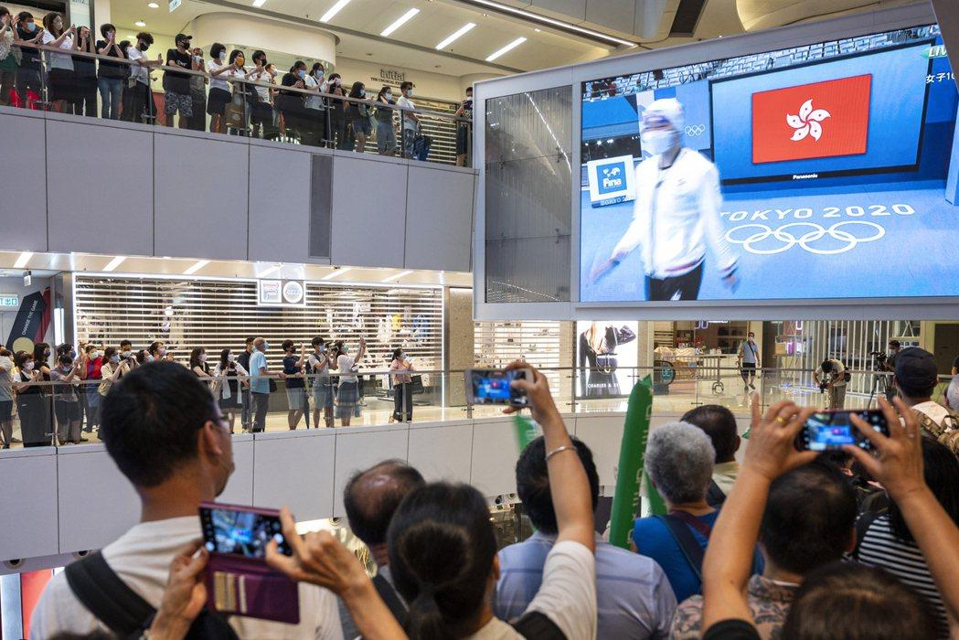 東京奧運期間,香港人們齊聚於百貨公司廣場的大螢幕前為游泳選手何詩蓓加油。 圖/歐新社