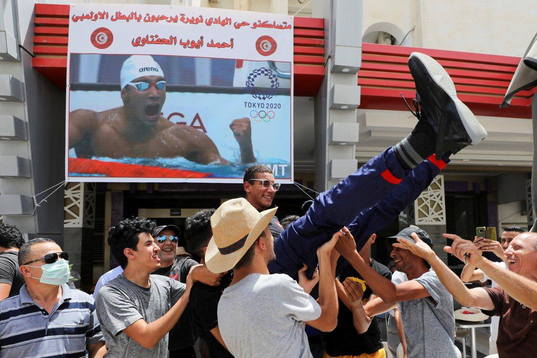 突尼西亞選手艾哈邁德.哈夫納維(Ahmed Hafnaoui)贏得東京奧運男子400公尺自由式金牌,他的親戚與粉絲將他抬起來慶祝。 圖/路透社