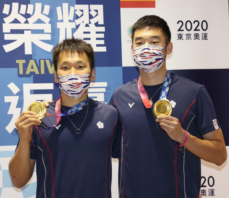 參加東京奧運的中華羽球代表隊昨天傍晚凱旋歸國,男子雙打奪得金牌的選手王齊麟(右)、李洋(左)一起秀出金牌。記者陳嘉寧/攝影 陳嘉寧