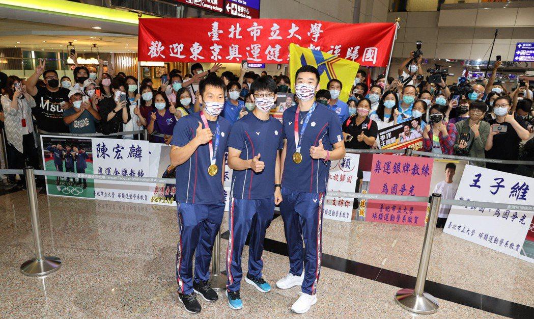 參加東京奧運的中華羽球代表隊昨天傍晚凱旋歸國,男子雙打奪得金牌的選手王齊麟(前排...