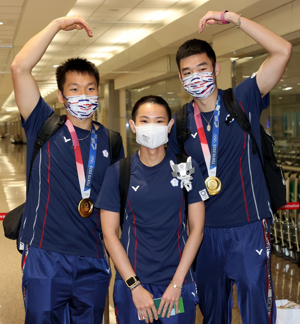 參加東京奧運的中華羽球代表隊昨天傍晚凱旋歸國,下機後三位奪牌選手王齊麟(右起)、...