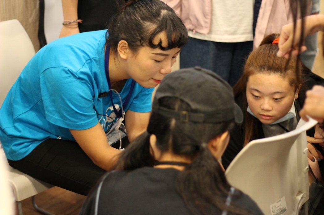 醒吾科大商設系學生江旻樺與同學認真討論資料,積極投入社團活動。 校方/提供