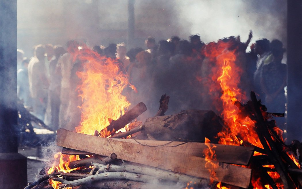 圖為印度露天火葬場示意圖。夏揚與他的3名隨從員工,就這樣架好了火葬木材堆,完全不...