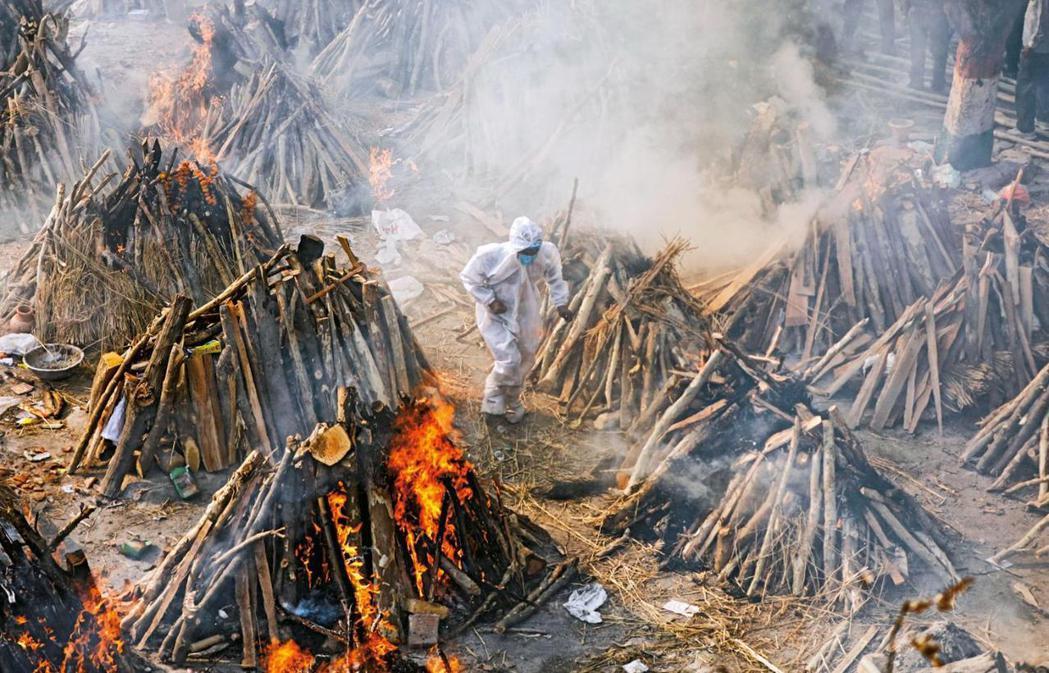 圖為印度露天火葬場示意圖,印度嚴峻疫情之下火葬場已經難以負荷,但卻仍接連有喪盡天...