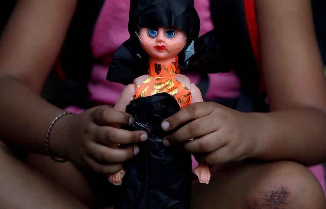 圖為2018年印度一場抗議性侵孩童的示威中,一名手捧著洋娃娃的女童。 圖/路透社
