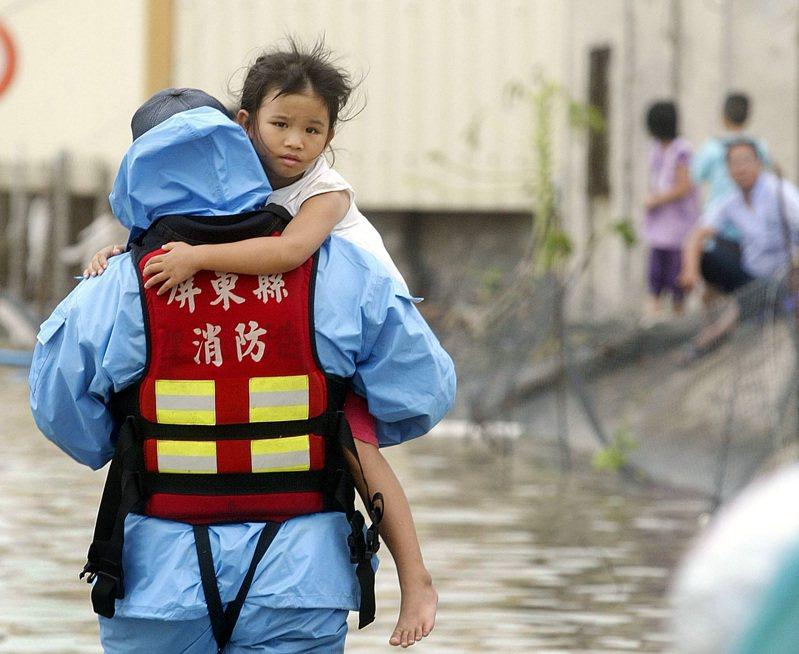 中颱「莫拉克」夾帶驚人雨量,使得屏東佳冬一帶,因適逢漲潮海水倒灌,淹水達一層樓高,災情慘重,一名小女孩一臉茫然無助地被救難人員抱著離開淹水區。圖/聯合報系資料照片