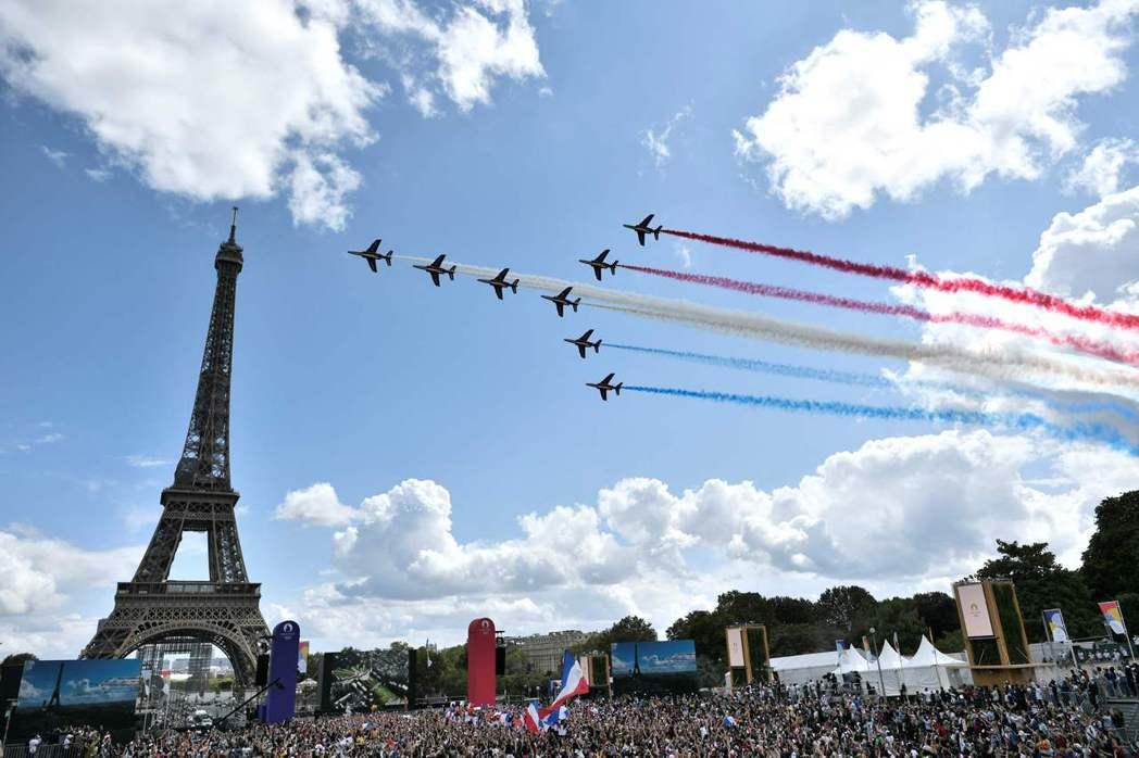 法國民眾八日在艾菲爾鐵塔前的托卡德洛廣場觀看東京奧運閉幕式的同時,也欣賞法國空軍...
