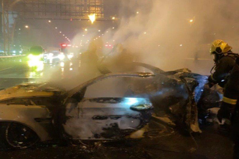 一輛BMW轎車在五股路段因大雨打滑自撞護欄,起火燒成廢鐵。記者林昭彰/翻攝