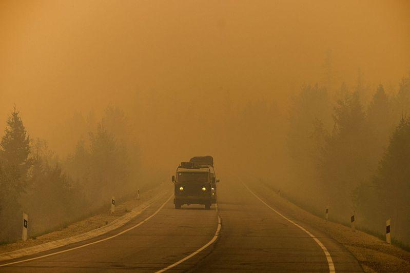俄國西伯利亞薩哈共和國一輛車7月27日在馬加拉斯村和雅庫茨克市間行駛,沿途被野火造成的煙霧籠罩。法新社