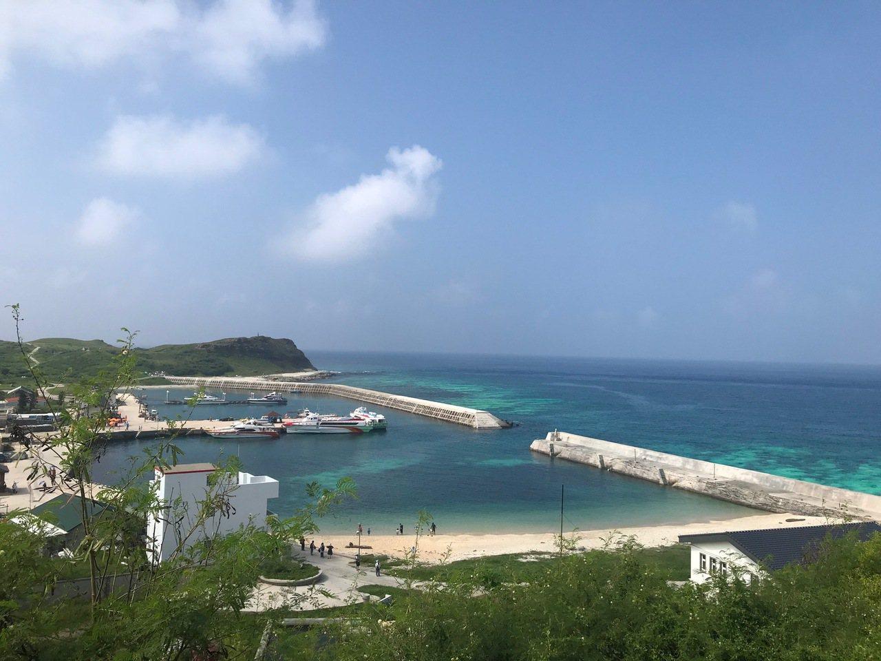 從高處俯瞰東吉嶼碼頭,海水呈現多層次變化,深淺不一的藍從海面擴散至天際。 圖/徐...