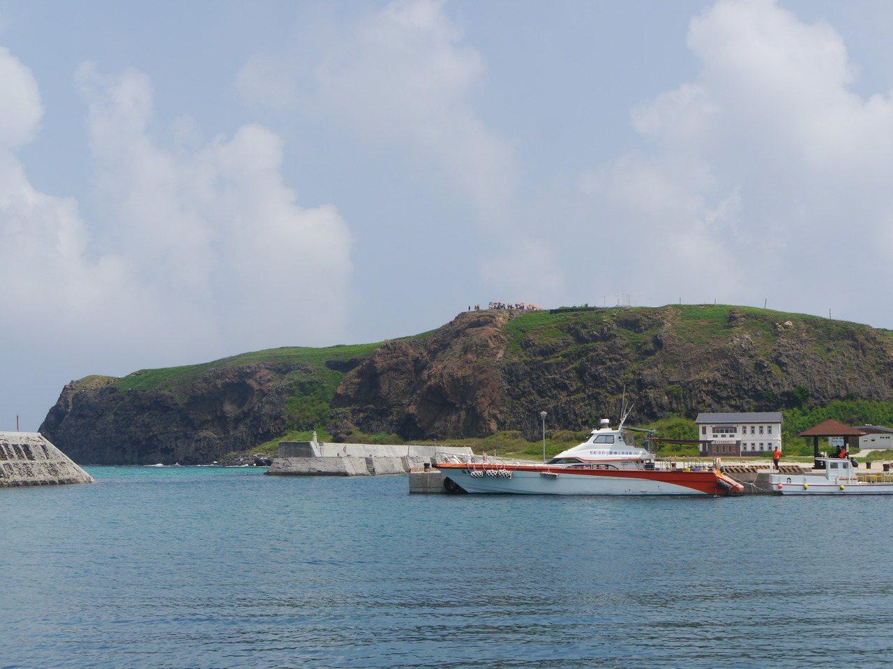 東吉嶼海面望去,遠方的玄武岩柱上有一個凹陷處,被稱為「東吉之眼」。 圖/徐白櫻 ...