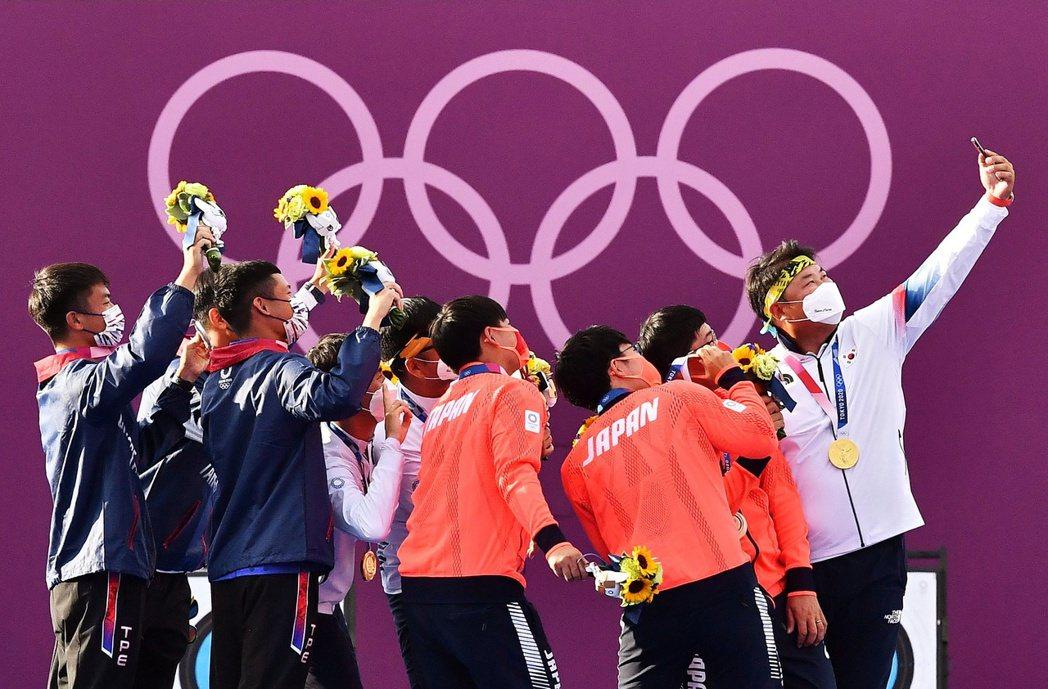 圖為本屆東京奧運男子團體射箭賽後,前三名合照。 圖/路透社