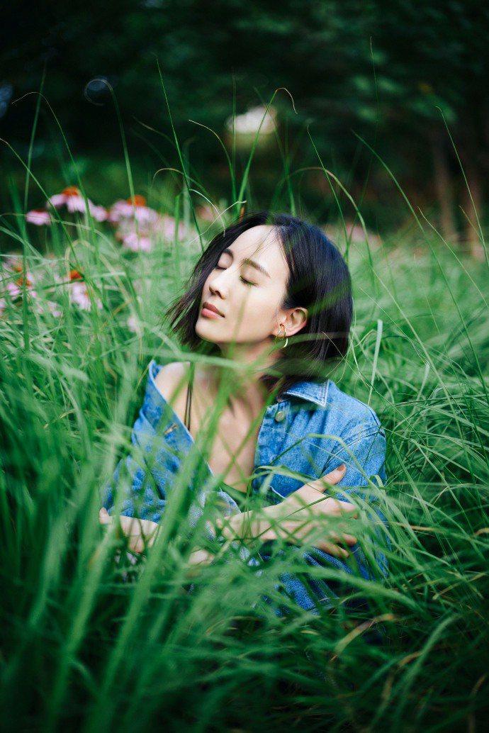 張鈞甯身穿LOEWE襯衫在綠草花叢間,斜露右肩展現微性感的情調。圖/取自微博