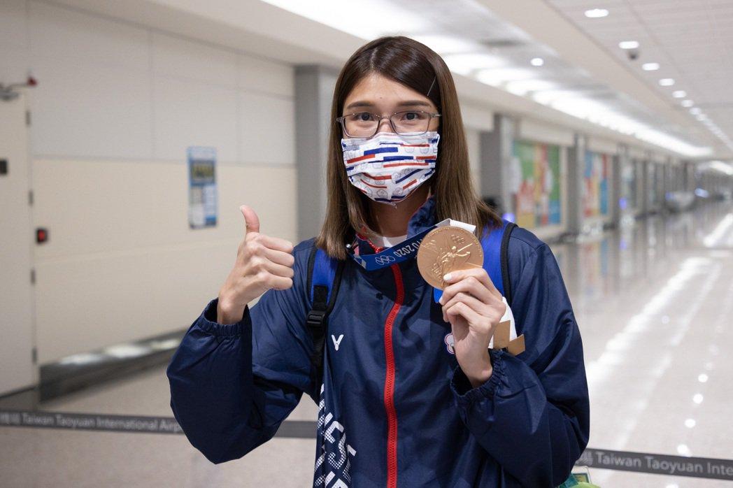 在東京奧運拳擊女子51公斤級奪得銅牌的黃筱雯返台後開心的舉起獎牌。記者季相儒/攝