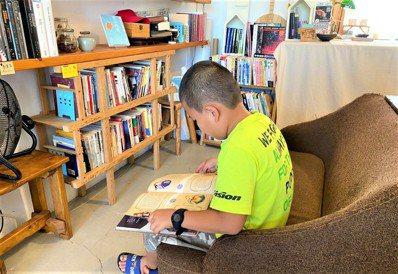 屏東縣恆春鎮紅氣球書屋是南屏東唯一的獨立書局,孩童坐在沙發享受閱讀。 圖/郭德慧...