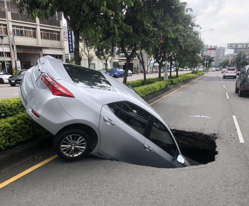 台中市文心南路東興路口路面,下午突出現1個大坑洞,林姓婦人駕車經過,因此掉入洞裡,車子卡在洞裡動彈不得,所幸警方據報趕到將女駕駛救出,送醫後並無大礙。圖/民眾提供