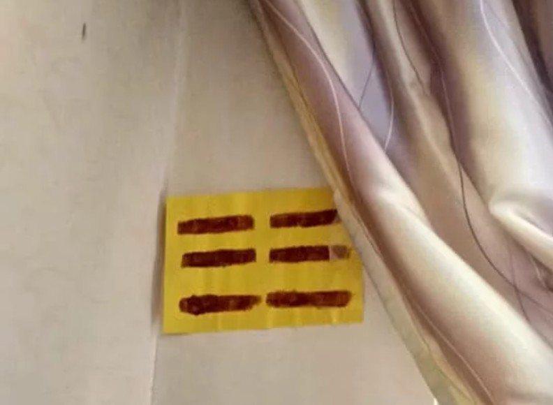 原PO發現窗簾底下貼著一張畫有6條橫線的黃紙。 圖/翻攝自「靈異公社」