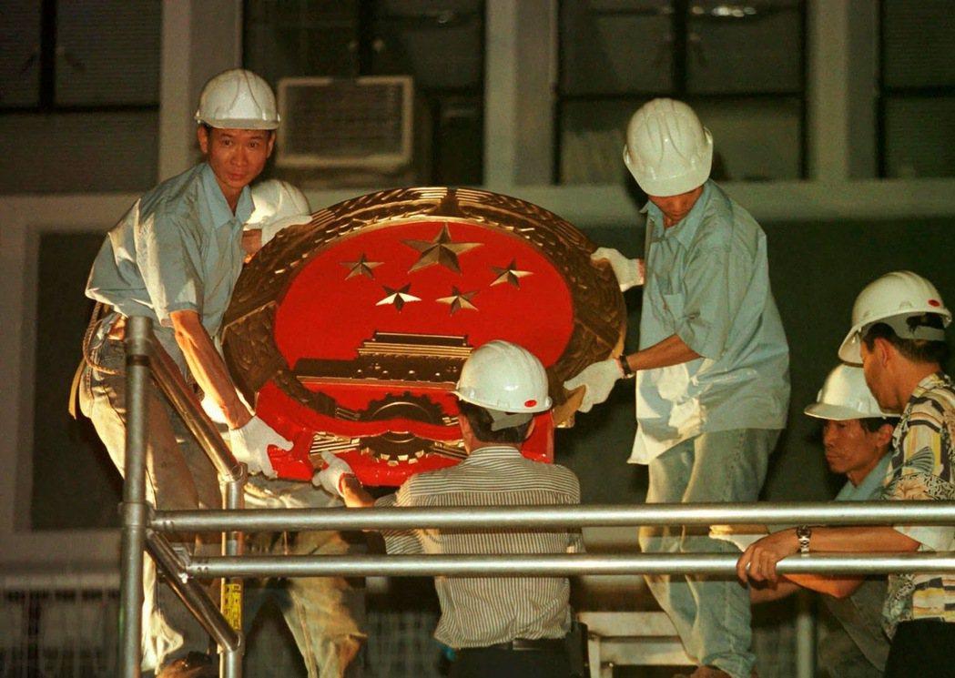 1997年7月1日,工人們於英國移交香港的儀式之後,在港府辦公室的牆上掛設新的中...