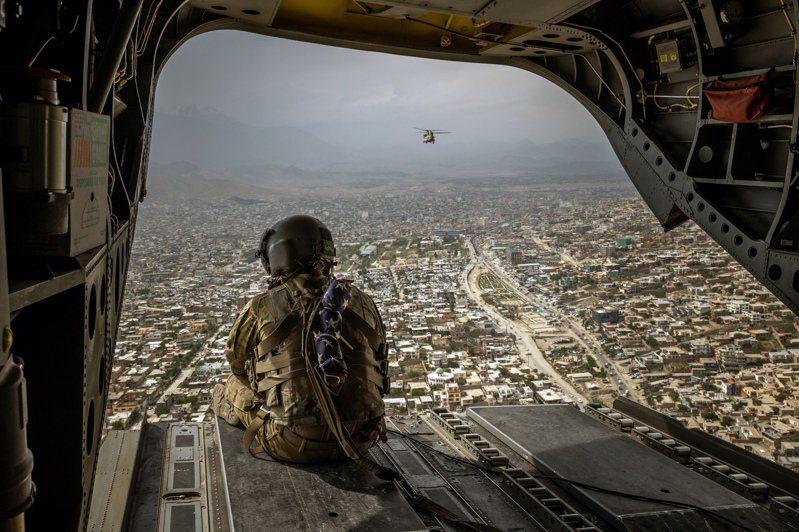 美國總統拜登曾說,美國人不能比伊拉克人更想要伊拉克民主,他對阿富汗也是同樣想法。圖為一名美軍官兵今年5月2日搭乘一架CH-47契努克直升機,在阿富汗首都喀布爾市上空飛航。圖/取自紐約時報