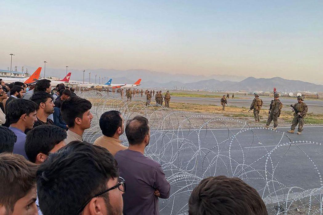 16日清早,美軍在喀布爾機場跑道上架起鐵絲網。 圖/法新社