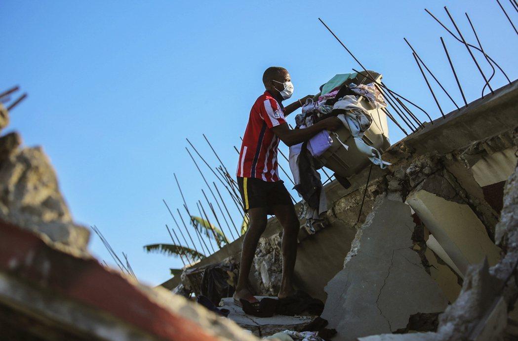 一名男子從家裡的殘骸中取出自己與家人的衣物。 圖/美聯社
