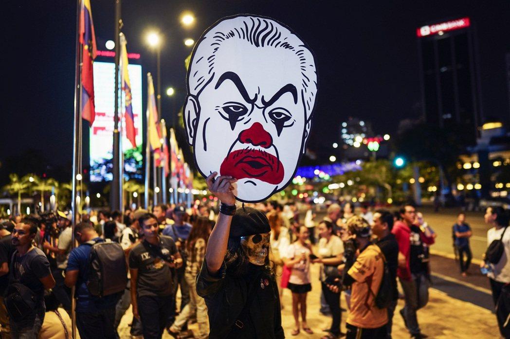 圖為民眾舉著反對慕尤丁首相的諷刺畫,譏諷其為後門政府。 圖/美聯社