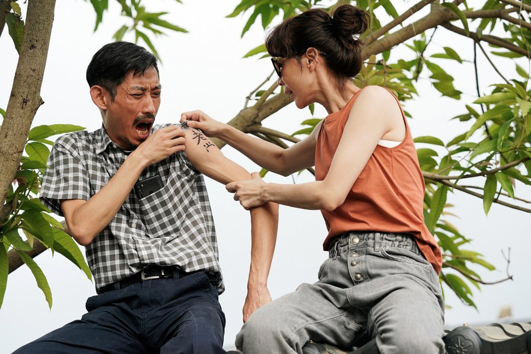 謝盈萱(右)看到老爸陳竹昇刺一半的刺青相當無奈。圖/華視、CATCHPLAY提供